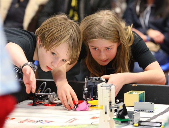 two students looking at lego robots