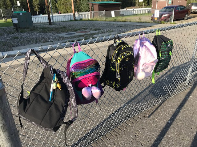 Four backpacks of varying size hanging on a fence in a school yard